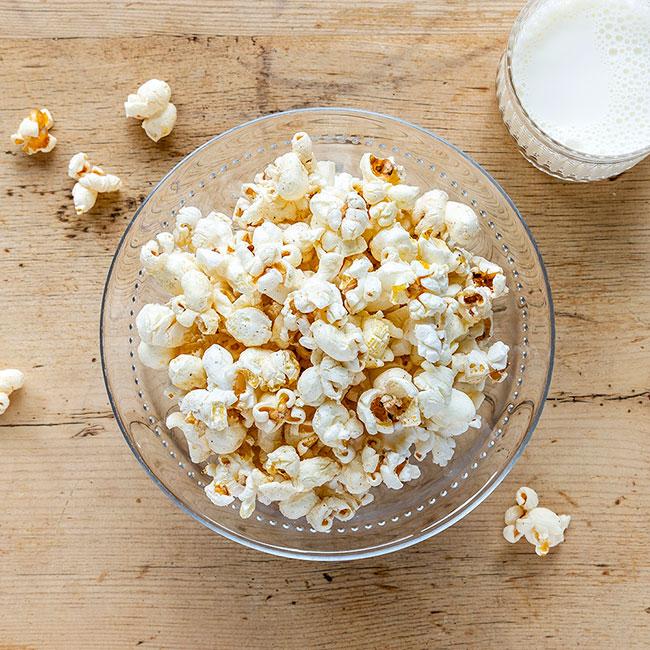 Salta popcorn med ett litet glas kall mjölk